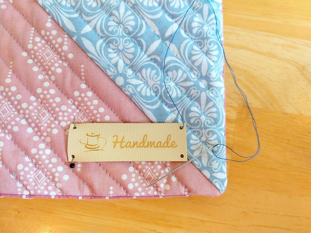 How to Make a Quilted Throw Pillow: Post 5: Sew the Pillow - leather label with text and symbol